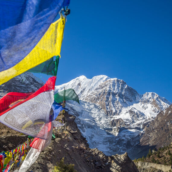 Nepal travel photography: Prayer flags flutter before Gangapurna, seen from the Annapurna Circuit.