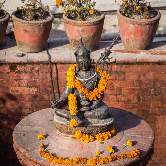 Nepal travel photography: A staue of Buddha draped with garlands at the Boudhanath Stupa in Kathmandu, Nepal.