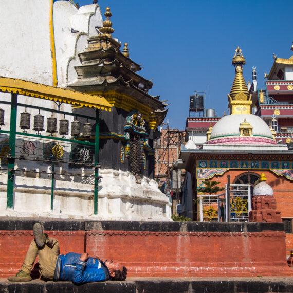 Nepal travel photography: A man sleeps below Kathesimbhu Stupa, Kathmandu, Nepal.