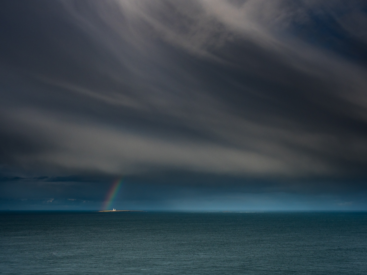 Travel photography Scotland: A rainbow frames Muckle Skerry Lighthouse in the Pentland Firth, near John o' Groats, Scotland.