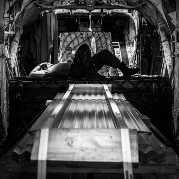 A Royal Canadian Air Force crewman rests atop cargo on a CC-130J Hercules aircraft on humanitarian aid operations in the Caribbean.