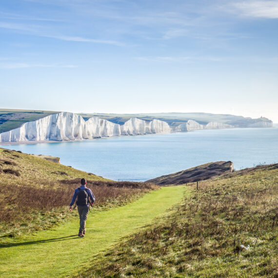 Travel photography England: A walker approaches the Seven Sisters, a famous chalk cliff formation in East Sussex, England, from nearby Seaford Head on 30 October 2017.