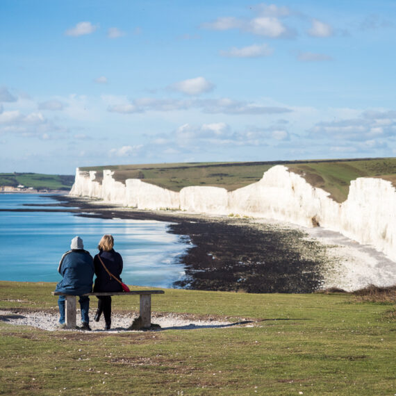 Travel photography England: Two tourists take in the view of the Seven Sisters, a chalk cliff formation in East Sussex, England, from nearby Birling Gap on 30 October 2017.