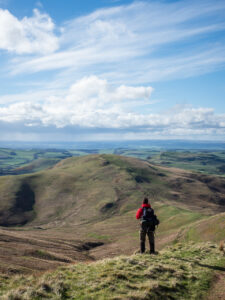 A man reviews scenery on the Pennine Way long-distance footpath through the Cheviot Hills on the border between England and Scotland on 26 April 2018.