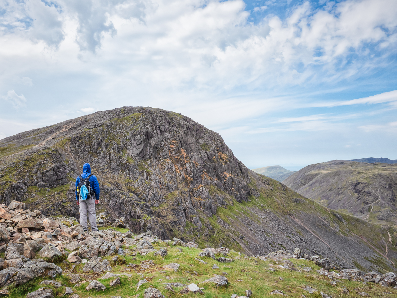 Travel photography England: A walker looks ahead to the mountain summit of Great Gable from Windy Gap in the Lake District, Cumbria, England.