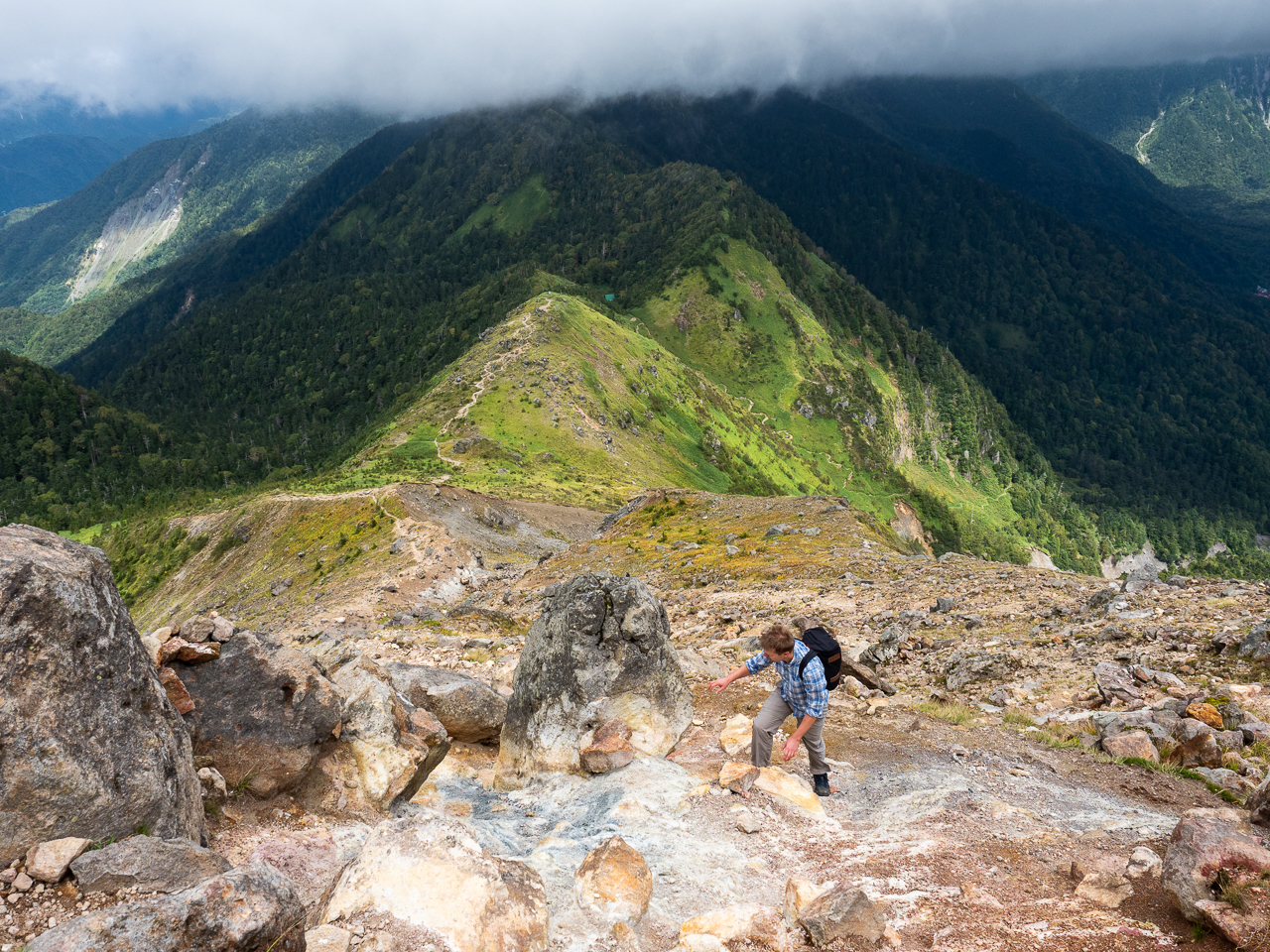 A hiker approaches the summit of Mount Yake, a volcano in Kamikōchi (the Upper Highlands) in the Hida Mountains, Nagano Prefecture, Japan.
