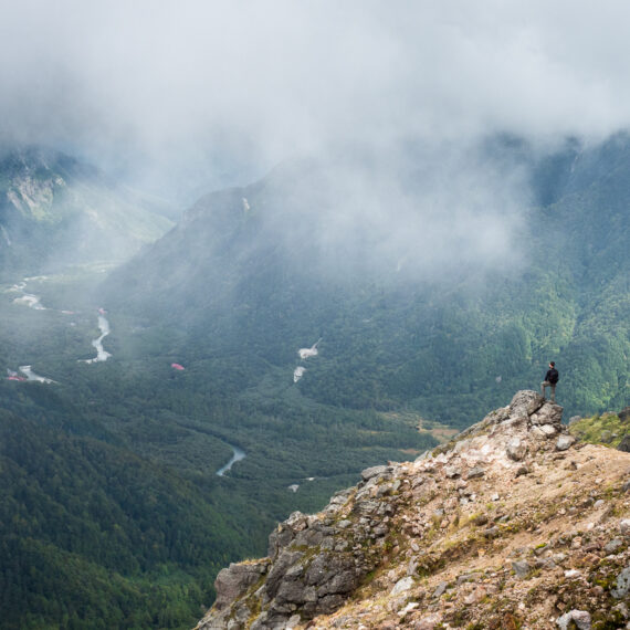 A hiker stands on a cloudy precipice on Mount Yake, a volcano in Kamikōchi (the Upper Highlands) in the Hida Mountains, Nagano Prefecture, Japan.