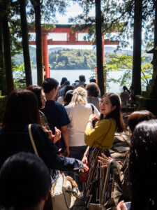 Tourists stand in line for selfies at the famous red lakeside torii (gate) at at the Hakone Shrine, Lake Ashi, Hakone, Japan.