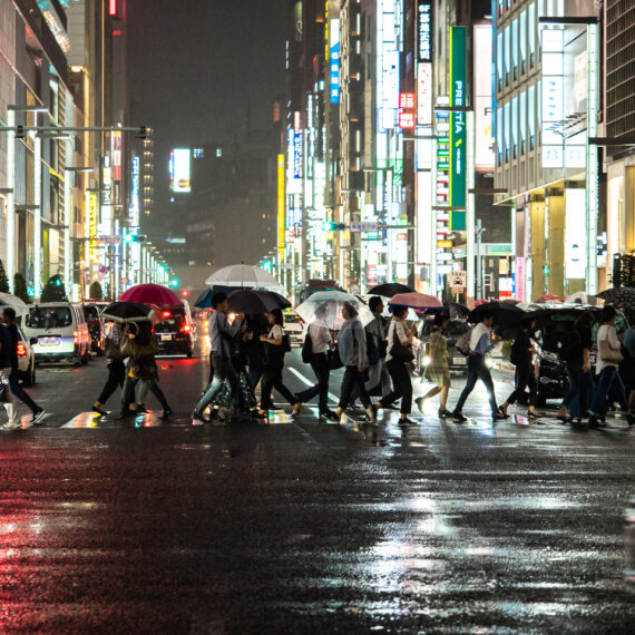 Japan travel photography: Pedestrians and vehicles at a main intersection on a rainy night in Ginza, Tokyo, Japan.