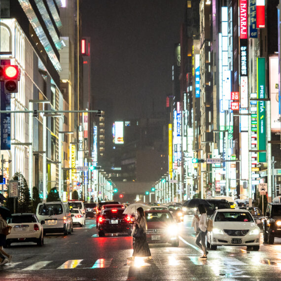 Pedestrians and vehicles at a main intersection on a rainy night in Ginza, Tokyo, Japan.
