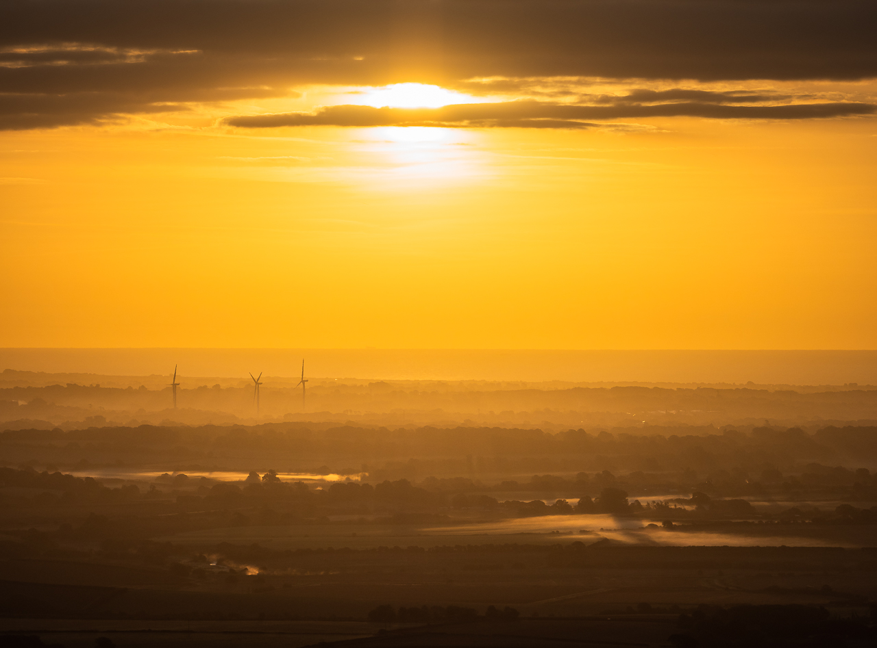 Wind turbines seen through mist at sunrise from Firle Beacon, a hill on the South Downs Way, East Sussex, England.