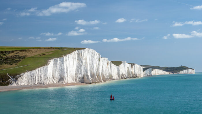 Travel photography England: A yacht with red sails seen in the English Channel by the Seven Sisters, chalk cliffs in East Sussex, England.