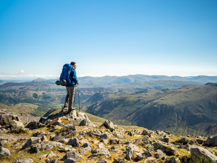 Travel photography England: A hiker views the horizon from Great Gable, a mountain in the Lake District, Cumbria, England.