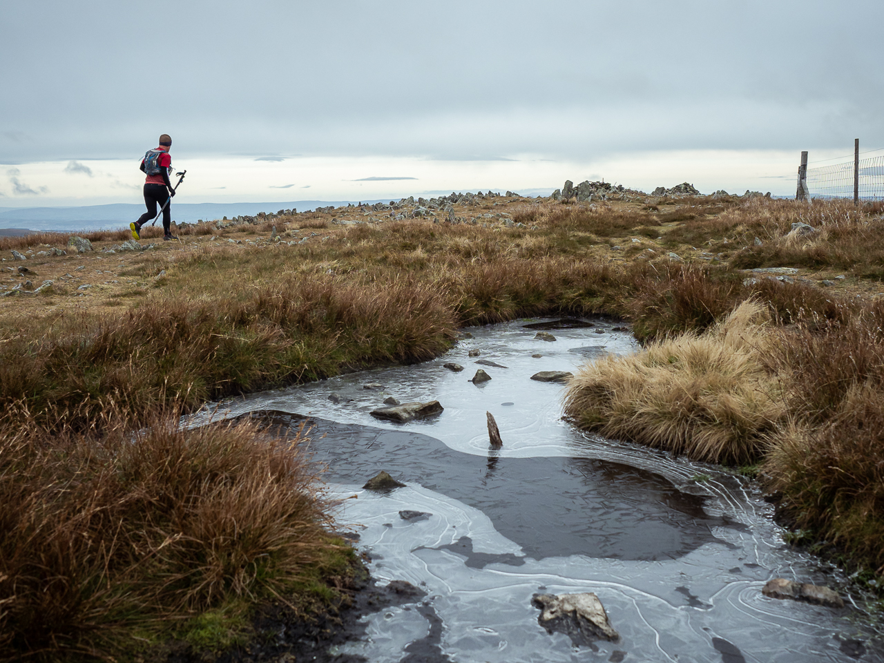 Kentmere Horseshoe: A fell runner dashes past a frozen pond near Harter Fell, in the Lake District, Cumbria, England.