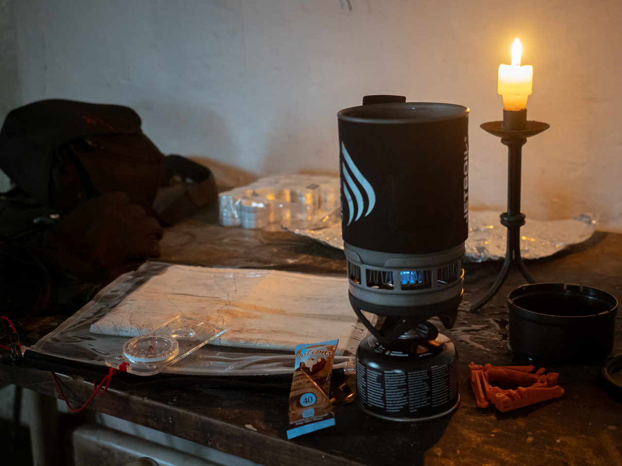 A Jetboil stove cooks food in Mosedale Cottage, a bothy in the Lake District, Cumbria, England.